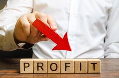 Businessman holds down arrow over word Profit. The concept of low profits in the company. Unprofitable business. Financial crisis stock image