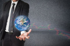 Businessman holds Earth in a hand with stock graph. Concept of r Royalty Free Stock Image