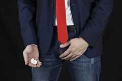 Businessman holds a groin, a handful of pills in her hand, prostatitis stock photo