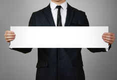 Businessman holds in hands a long, narrow paper. Empty for your text.  on gray background Royalty Free Stock Photo