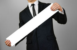 Businessman holds in hands a long, narrow paper. Empty for your text. Isolated on gray background. Royalty Free Stock Photos