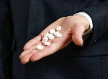 Businessman holds in hands a lot of white pills and packs of tablets Royalty Free Stock Image