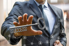 Businessman holds his hand out to take the key of success. stock photo