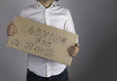 Businessman holds the inscription - Looking for a job.  Royalty Free Stock Image