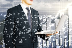 Businessman holds laptop with flying numbers at business chart b Royalty Free Stock Image