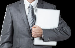 Businessman holds  laptop. Businessman in grey suite holds laptop Stock Photos