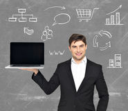 Businessman holds  laptop with icons Stock Photo