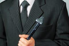 Businessman holds metal crowbar Stock Images