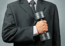 Businessman holds metal dumbbell Stock Photo