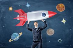 A businessman holds a model of a retro rocked above his head near drawings of planets and stars. stock photo