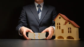 Businessman holds a money stack near a house model on a table Royalty Free Stock Images