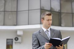 Businessman holds the notebook. On the building background Royalty Free Stock Photography