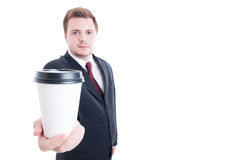 Businessman holds and offer a coffee to go cup Royalty Free Stock Photos
