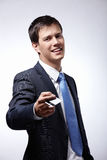 Businessman holds out a credit card. A young businessman holds out a credit card royalty free stock images