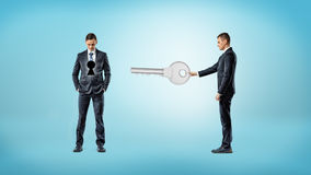A businessman holds out a giant key in the direction of another man who has a dark keyhole on his torso. Stock Images
