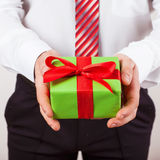 Businessman holds out the gift box Royalty Free Stock Photos