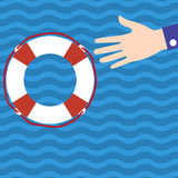 Businessman holds out his hand for help to the lifebuoy in the w Stock Photo