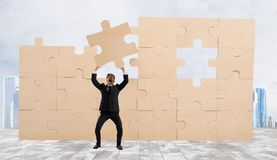 Businessman with a piece of puzzle. Build the business concept Stock Photos