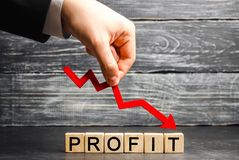 A businessman holds a red arrow to down and the inscription `profit`. Unsuccessful business and poverty. Profit decline. Loss of i royalty free stock photo