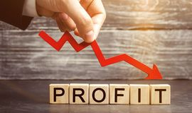 A businessman holds a red arrow to down and the inscription profit. Unsuccessful business and poverty. Profit decline. Loss of. Investment. Low wages. Economic stock photo