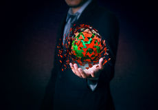 Businessman holds red and green explosion in hand on background. Stock Image