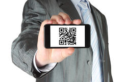 Businessman holds smart phone with QR code Royalty Free Stock Images