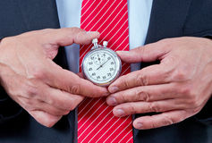 Businessman holds stopwatch Royalty Free Stock Images