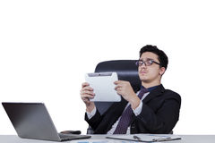 Businessman holds tablet and lean on office chair Royalty Free Stock Photography