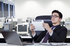 Businessman holds tablet and leans on office chair. Middle eastern entrepreneur leans on the office chair while holding a digital tablet with laptop computer on Stock Photos