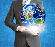 Businessman holds tablet pc with Earth in hand Royalty Free Stock Image