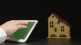 Businessman holds a tablet PC at the hands near a house model on a table (green screen). Businessman holds a tablet PC at the hands near a house model on table ( stock video