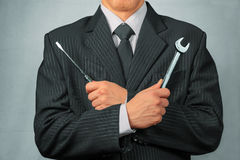 Businessman holds tools, concept of business creation. Businessman in a suit holds metal wrench and screwdriver, concept of business creation Stock Photography