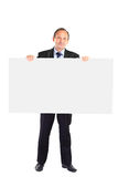 Businessman holds up a blank white sheet. Royalty Free Stock Photography