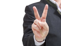 Businessman holds victory sign - hand gesture. Businessman holds victory sign close up - hand gesture isolated on white background Stock Image