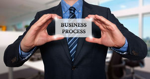 Businessman holds white card with Business Process sign, Office-. Stock Photo Royalty Free Stock Photography