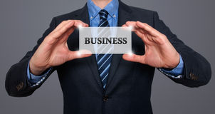 Businessman holds white card with Business sign, Grey - Stock Ph Stock Images