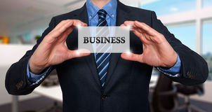 Businessman holds white card with Business sign, Office - Stock Royalty Free Stock Photo