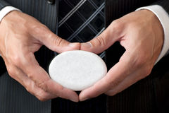 Businessman Holds White Concept Stone At Belt Leve. A close-up shot of a well dressed businessman displaying the face of a white concept stone at belt level stock images
