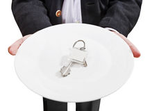 Businessman holds white plate with new door keys. Front view of businessman holds white plate with new door keys isolated on white background stock photography