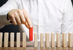 Businessman holds a wooden block in his hands. The concept of personnel selection and management within the team. Dismissal and stock images