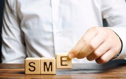 Businessman holds wooden blocks with the word SME. Small and medium-sized enterprises - commercial enterprises that do not exceed royalty free stock photography