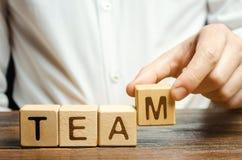 Businessman holds wooden blocks with the word Team. Team management concept. Teamwork. Hiring. Recruitment staff. Work in stock photo