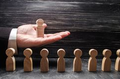 A businessman holds a wooden leader figure on the palm of his hand over a number of other workers. Concept leader, team work. Business and department stock photos