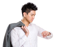 Businessman holing jacket and looking at watch Stock Photography