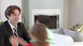 Businessman Home From Work Greeted By Children. Father dressed in suit kneels down in family lounge and children rush to greet him. Shot on Canon 5d Mk2 with a stock footage