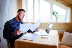 Businessman at home, he is working with a laptop, checking paperwork and bills.  royalty free stock photos