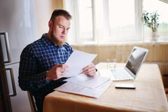 Businessman at home, he is working with a laptop, checking paperwork and bills.  royalty free stock photography