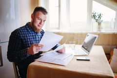 Businessman at home, he is working with a laptop, checking paperwork and bills.  royalty free stock photo