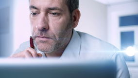 Businessman at home. Businessman working at home with laptop / tablet, holding pen - tracking shot stock footage