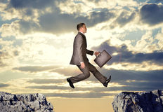 Businessman hopping over abyss Royalty Free Stock Image